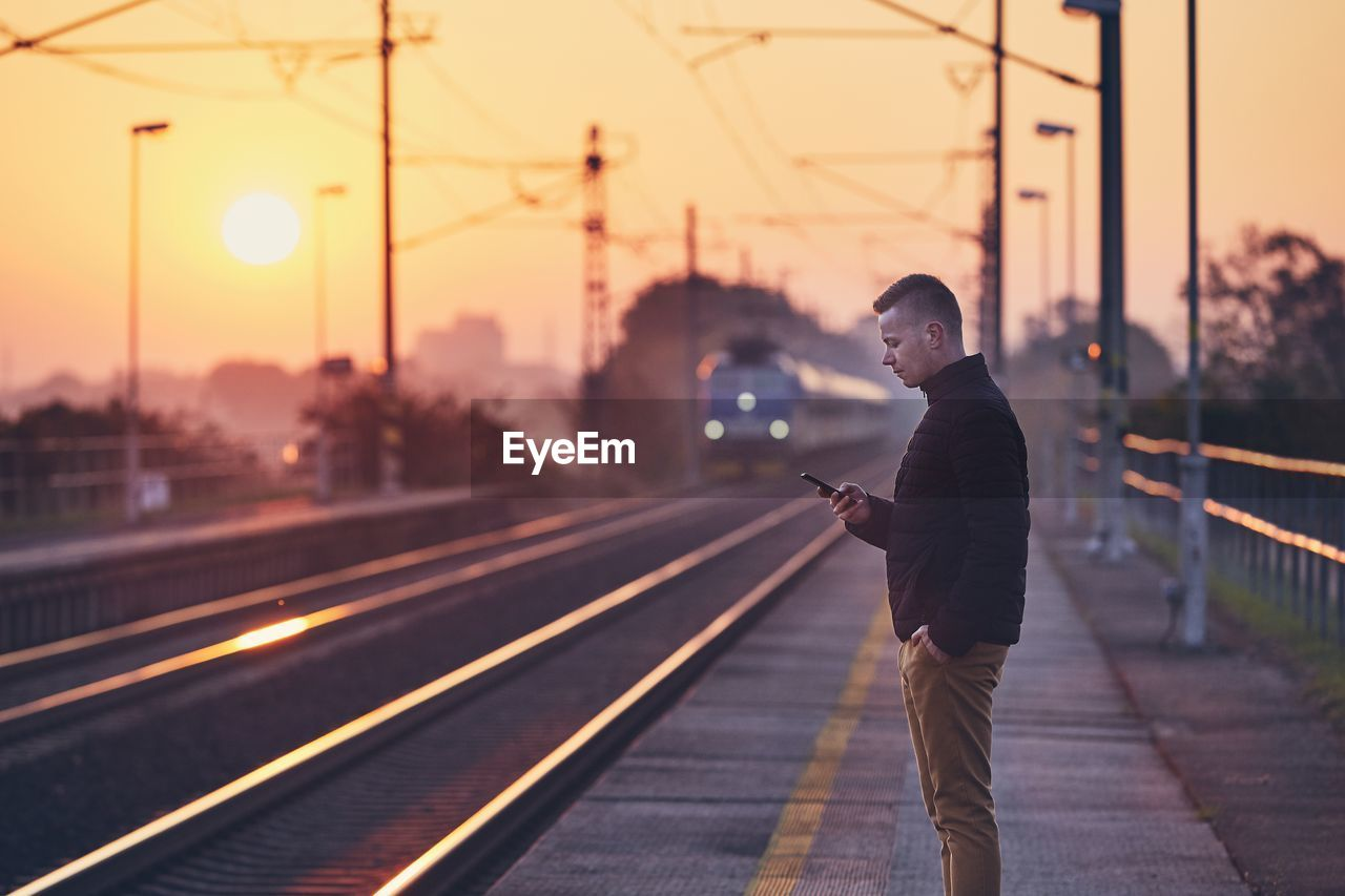 Side View Of Man Standing At Railroad Station Against Sky During Sunset