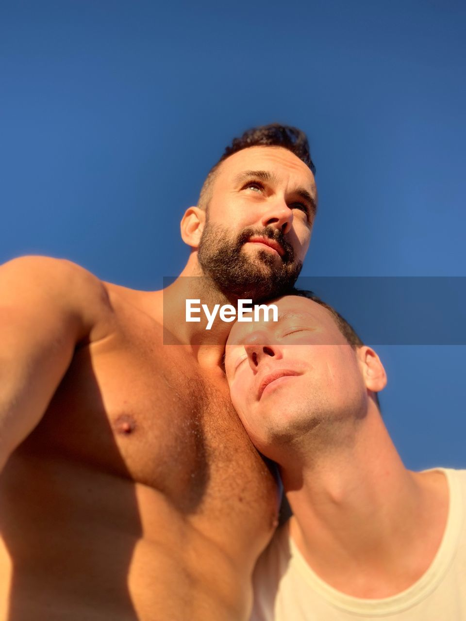 Low Angle View Of Gay Men Against Blue Sky During Sunny Day