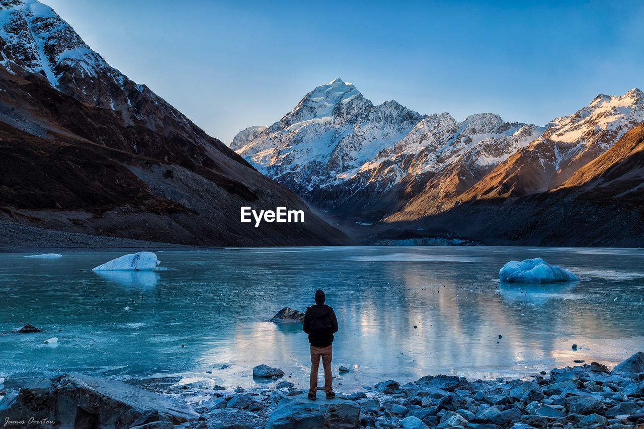 Rear View Of Man Standing By Lake Against Snowcapped Mountain