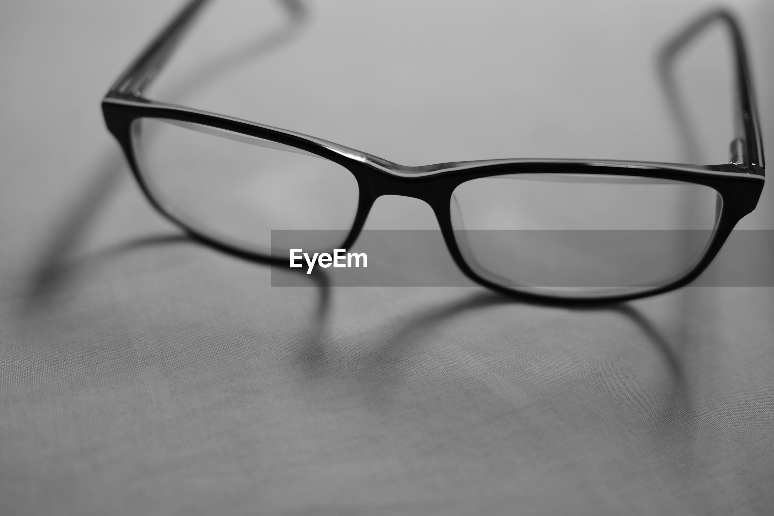 CLOSE-UP OF EYEGLASSES ON GLASS TABLE