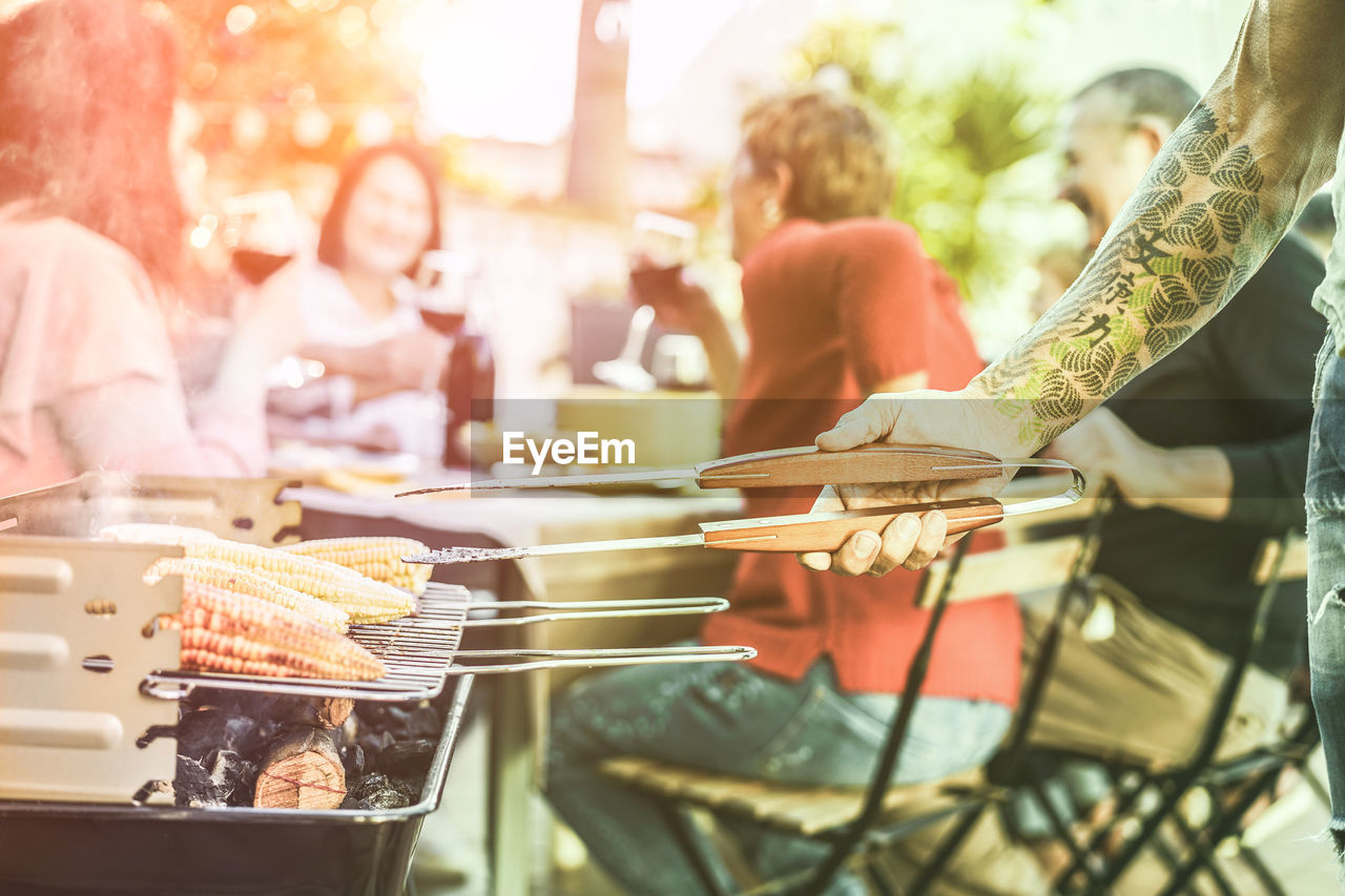group of people, incidental people, food and drink, food, real people, medium group of people, men, women, selective focus, crowd, adult, market, day, retail, lifestyles, group, people, focus on foreground, city, emotion, outdoors, consumerism