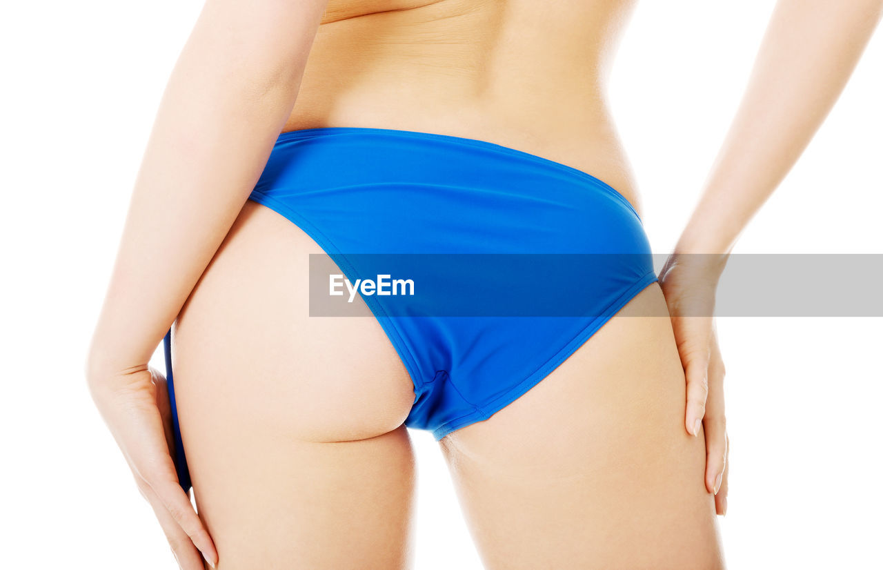 Midsection of seductive woman wearing blue panties while standing over white background