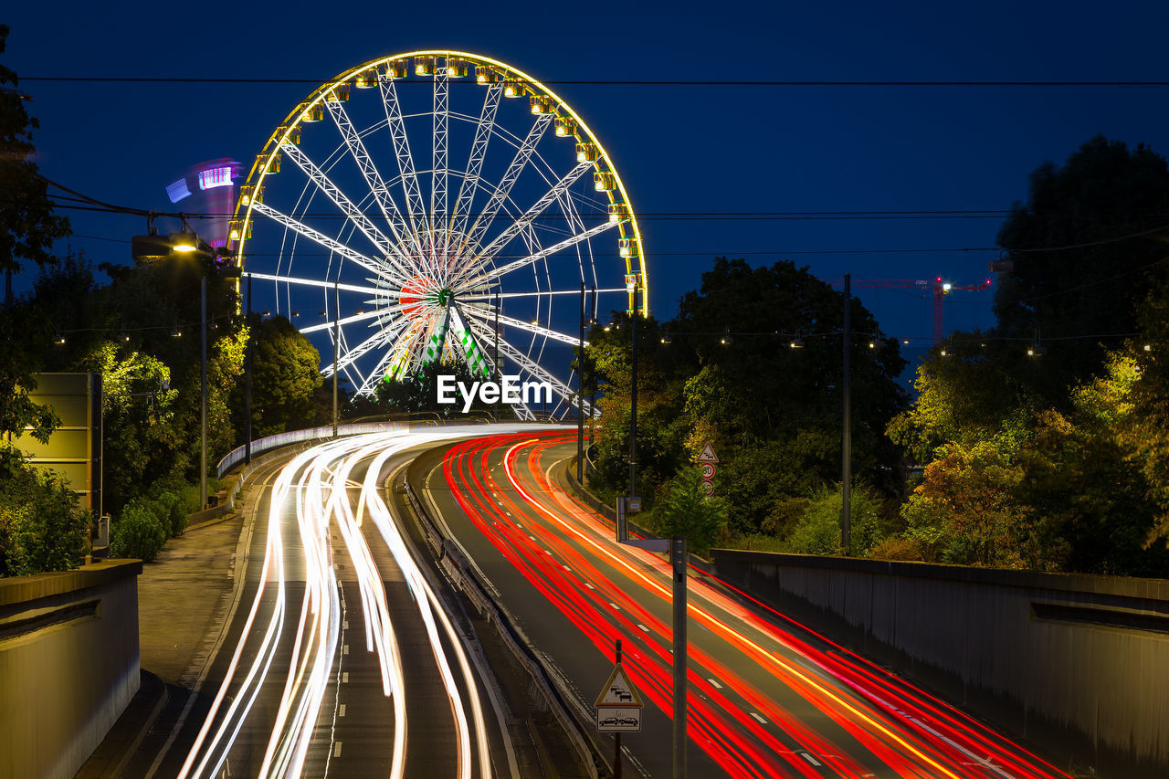 illuminated, speed, motion, night, long exposure, tree, blurred motion, light trail, transportation, road, no people, nature, sky, glowing, architecture, city, plant, built structure, red, connection, outdoors, multiple lane highway