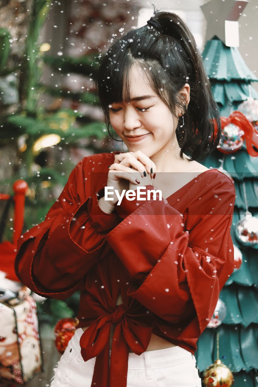 Christmas portrait of a beautiful smiling girl with closed eyes enjoying winter  on the snowy day