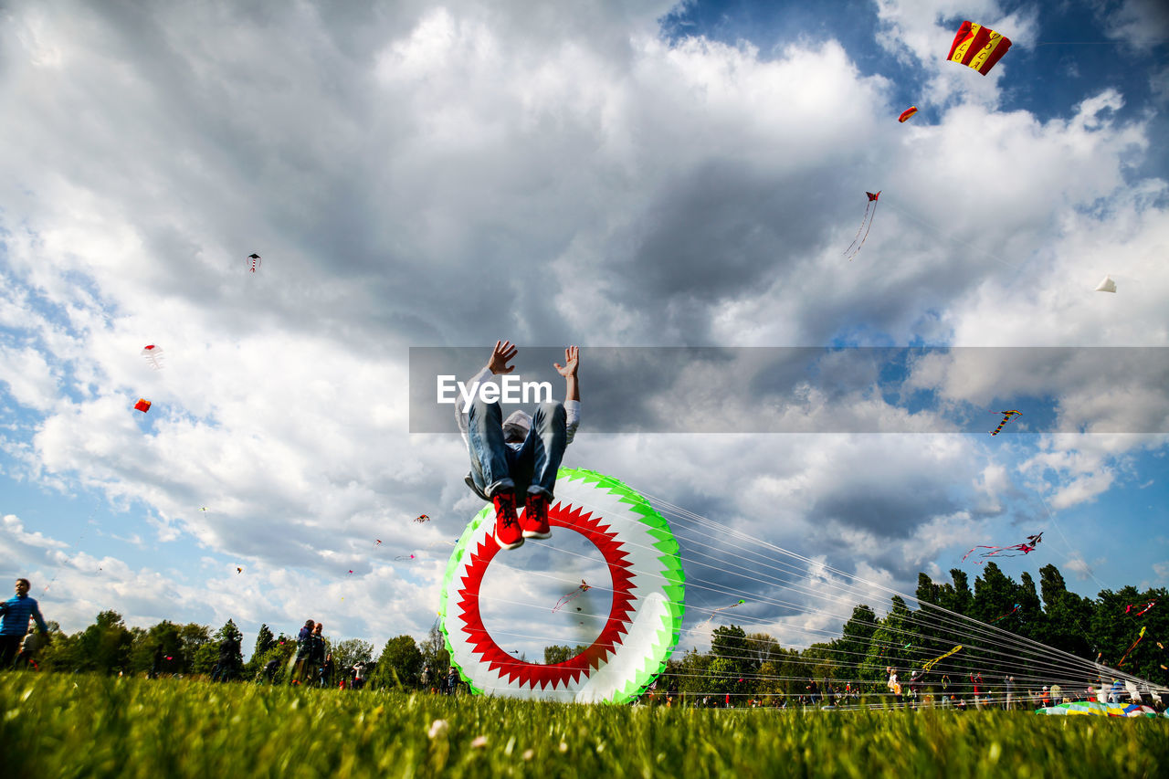 Man Performing Somersault By Parachute Against Sky