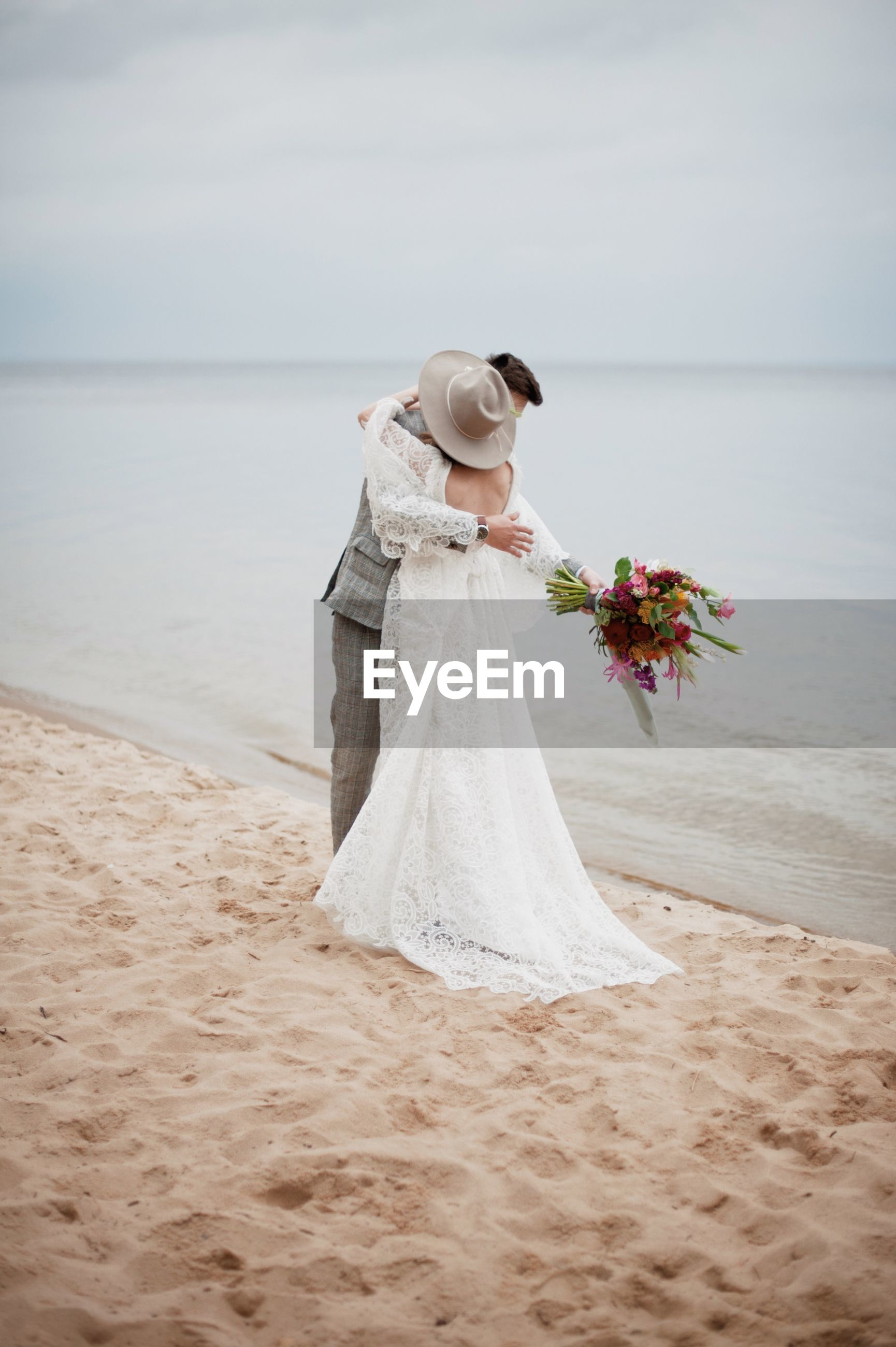 Bride and bridegroom embracing at beach during wedding ceremony