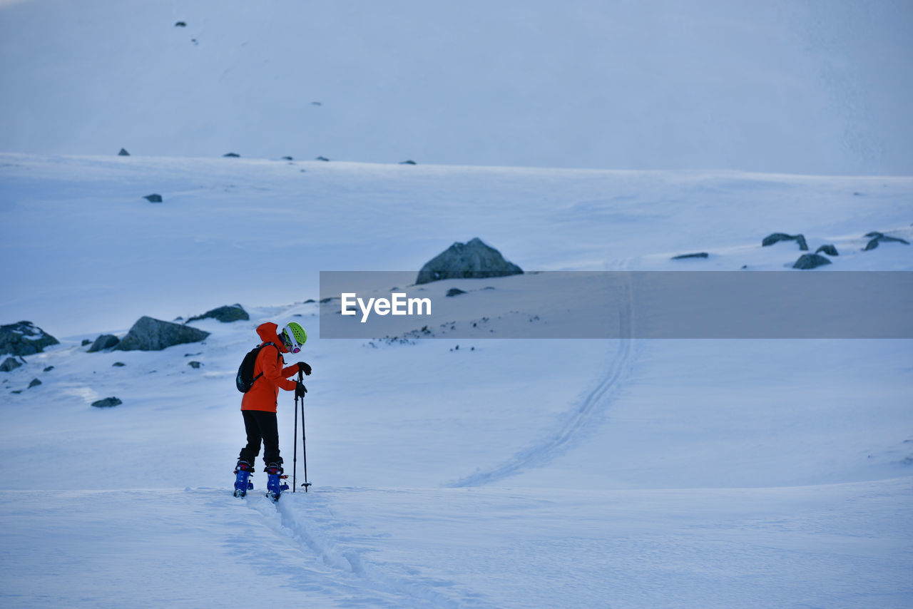 Rear View Of Person Skiing On Snow Covered Landscape Against Sky