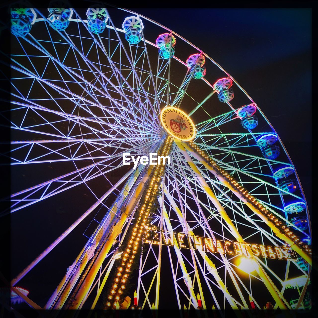 ferris wheel, amusement park, amusement park ride, illuminated, night, arts culture and entertainment, low angle view, fairground, sky, no people, leisure activity, circle, outdoors, large, shape, glowing, geometric shape, nature, transfer print, spinning