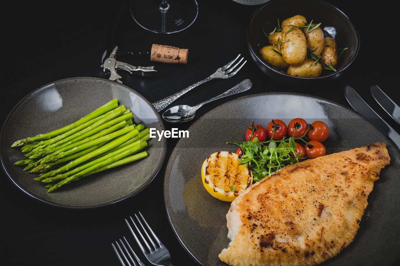 food, food and drink, vegetable, healthy eating, freshness, ready-to-eat, indoors, wellbeing, still life, fork, kitchen utensil, fruit, eating utensil, high angle view, table, tomato, plate, no people, household equipment, bowl, black background, snack
