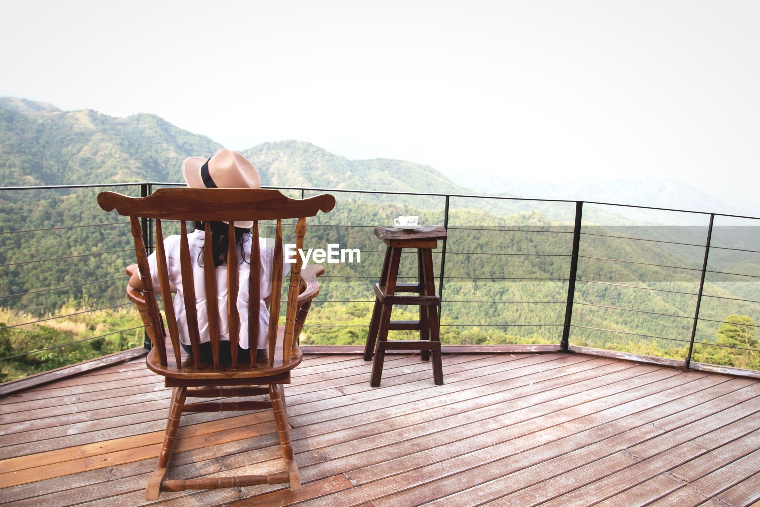 Woman sitting on chair against mountains