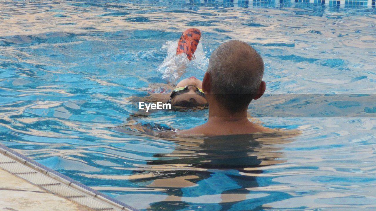 Man with son swimming in pool