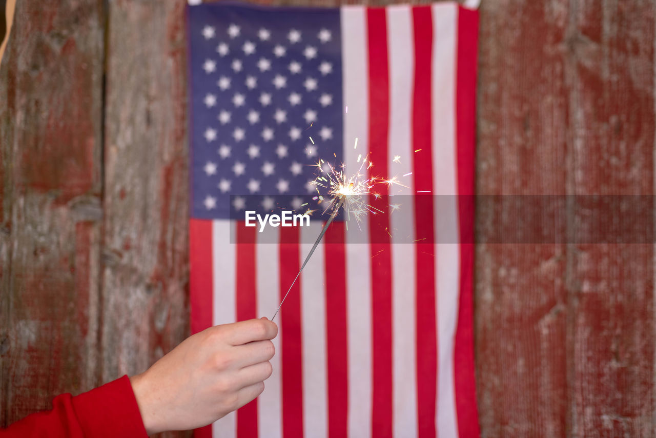 Cropped hand holding lit sparkler against american flag on wall