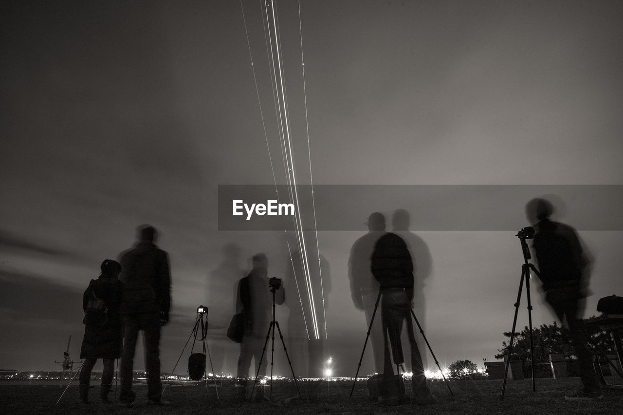 Double Exposure Of People Standing By Cameras On Tripod Against Sky