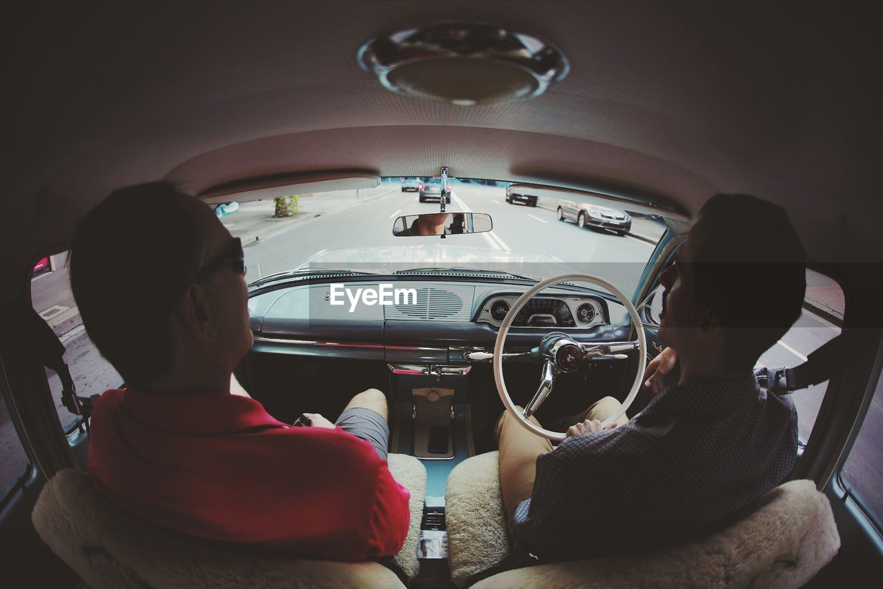 REAR VIEW OF MEN IN THE CAR