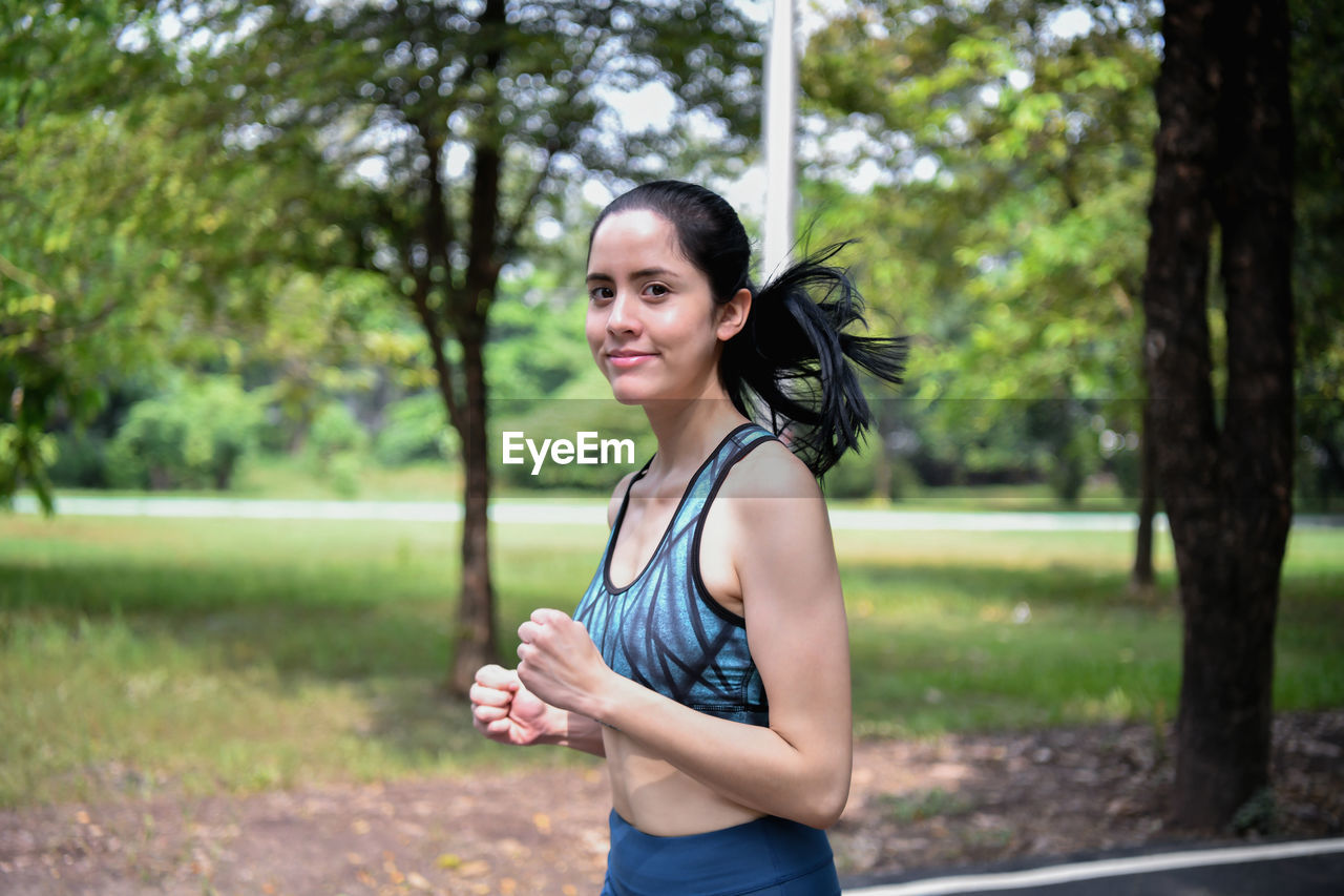 Smiling Young Woman Exercising In Park