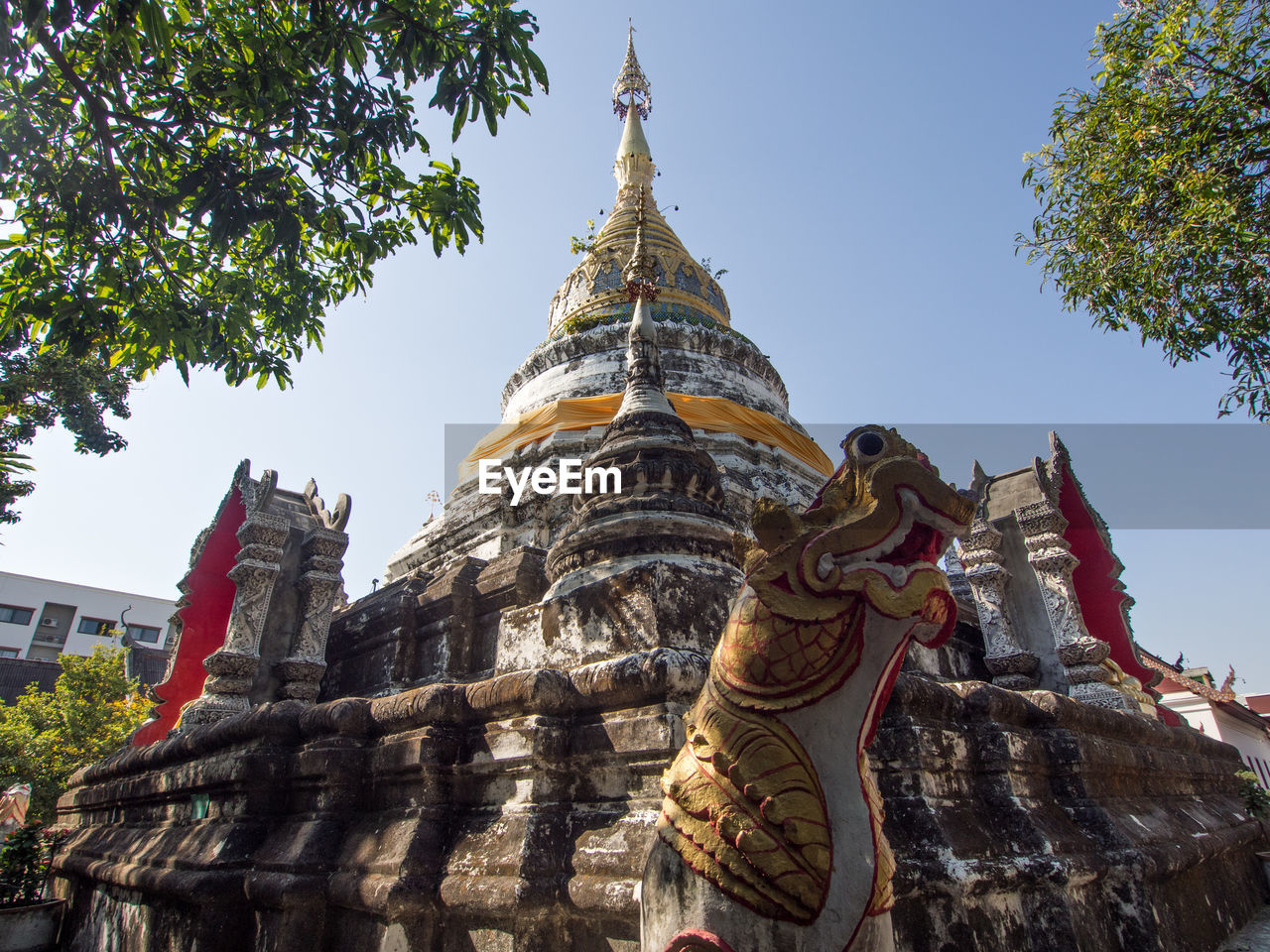 religion, spirituality, place of worship, architecture, statue, building exterior, built structure, pagoda, low angle view, sculpture, history, ancient, day, travel destinations, sky, outdoors, no people, tree, clear sky