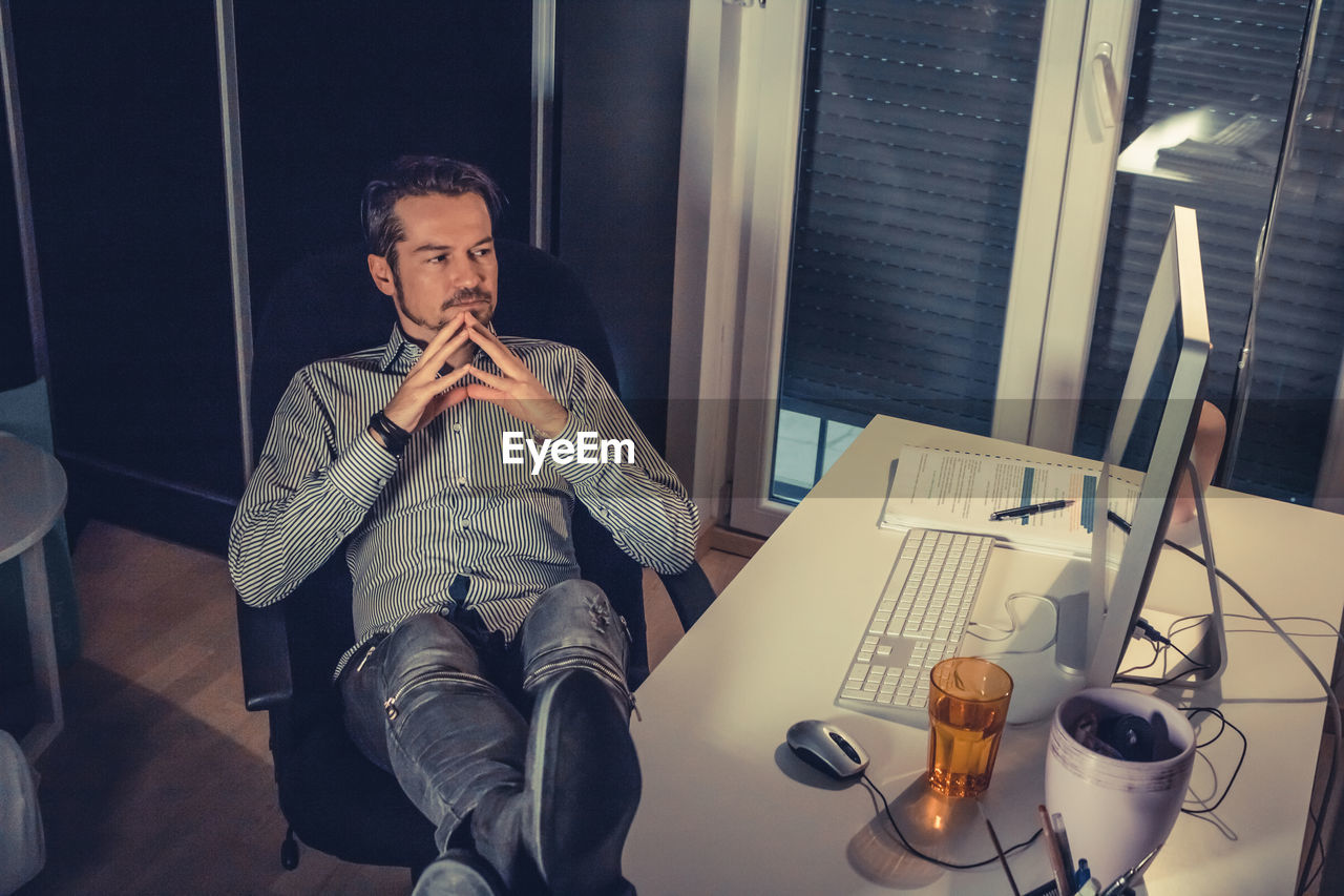 Tired businessman using computer in office