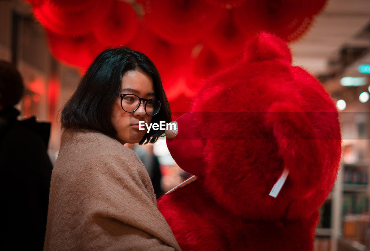red, one person, portrait, lifestyles, real people, leisure activity, focus on foreground, mid adult, young adult, headshot, glasses, adult, eyeglasses, women, looking, indoors, mid adult women, young women, hairstyle, warm clothing, contemplation