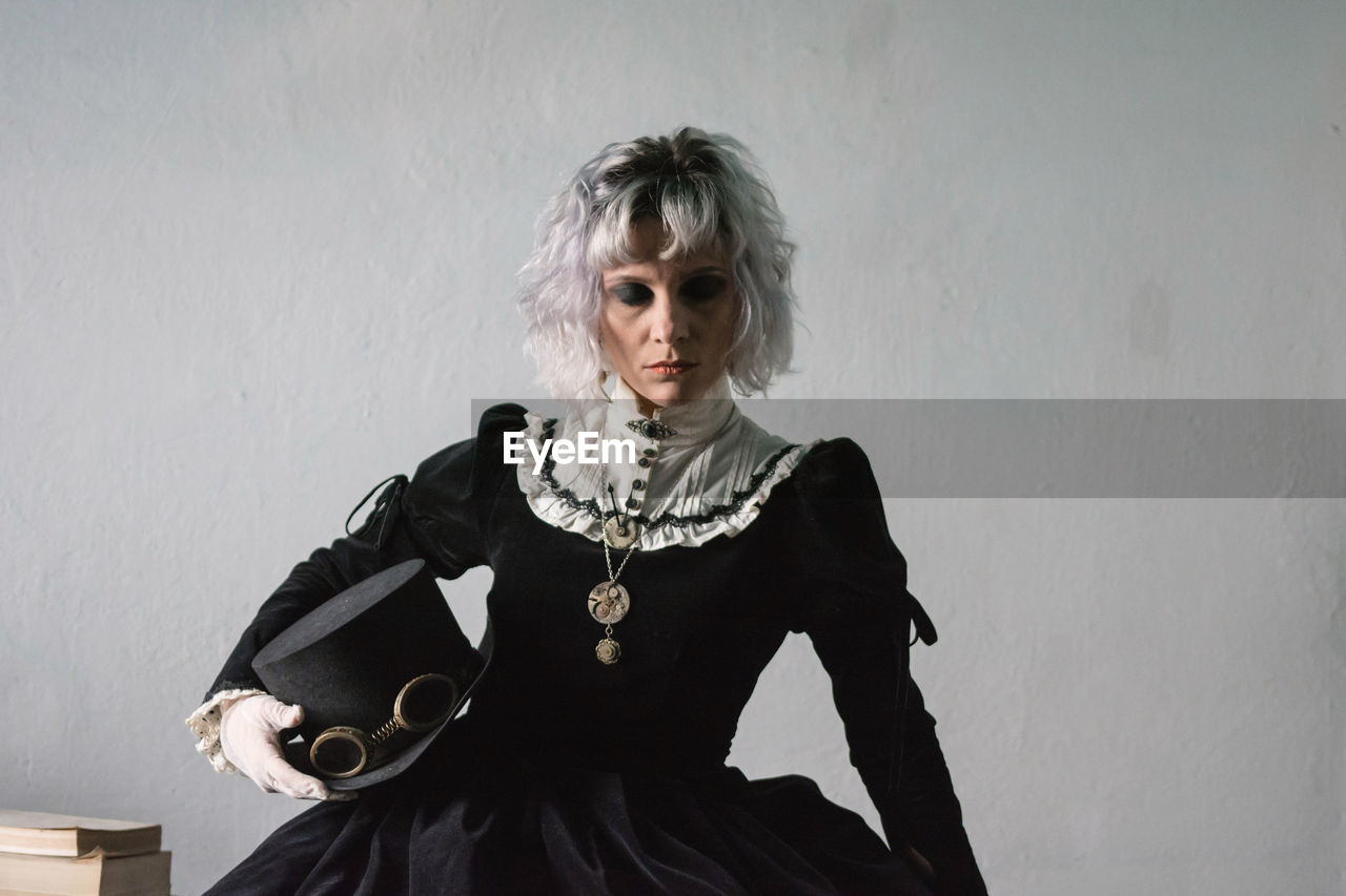 Woman wearing costume while sitting against wall at home