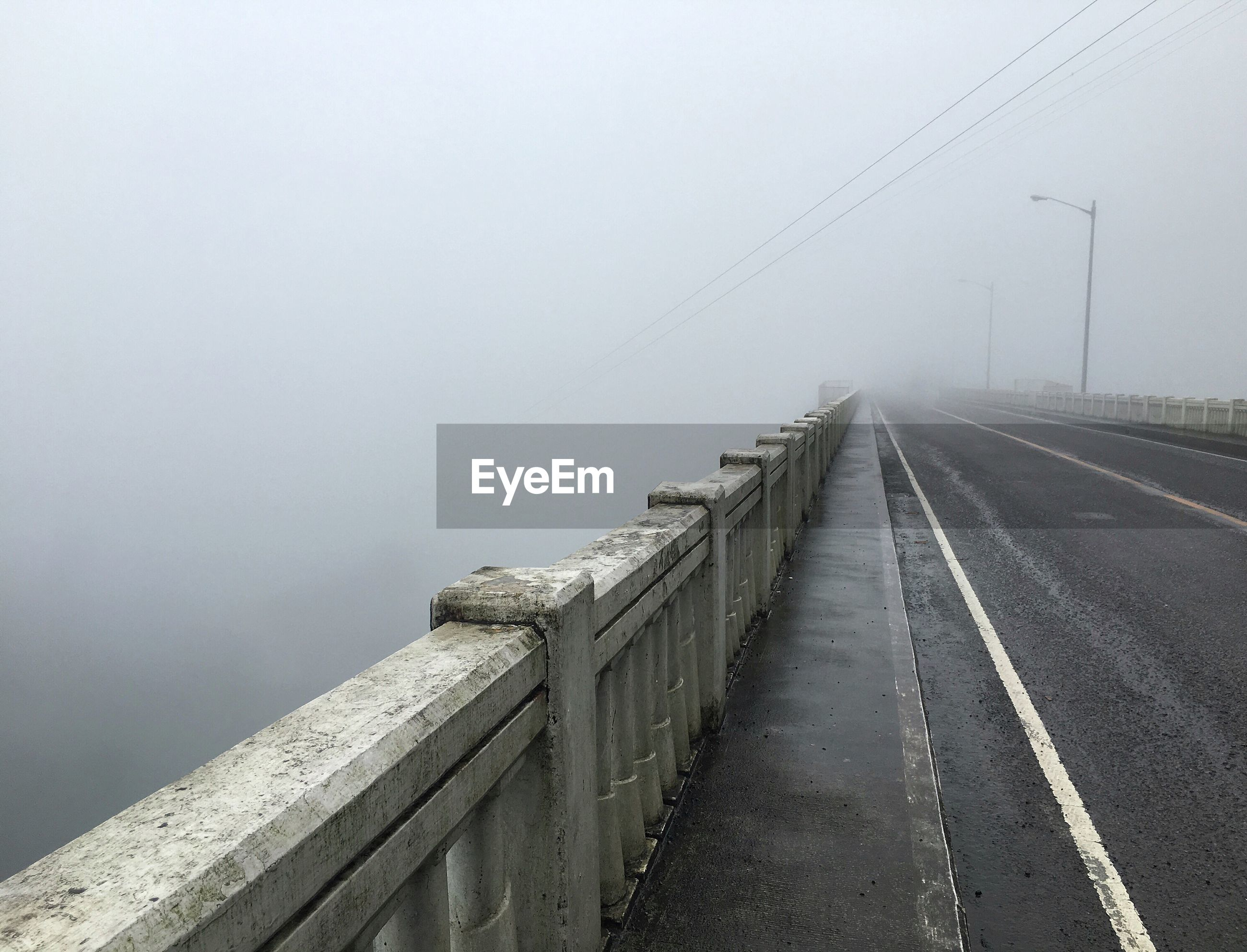 BRIDGE OVER FOGGY WEATHER AGAINST SKY
