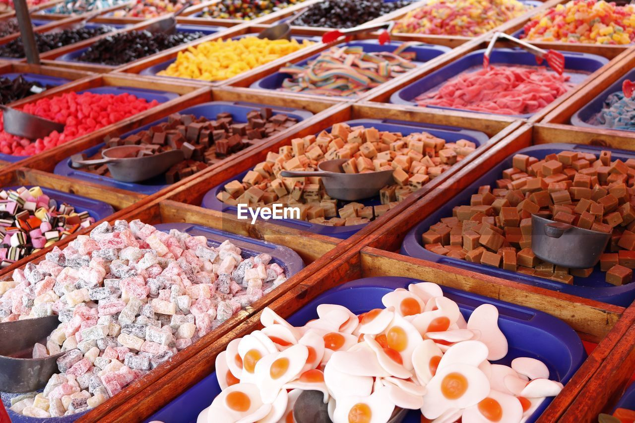 food and drink, food, variation, large group of objects, retail, abundance, choice, arrangement, for sale, freshness, no people, high angle view, sweet food, in a row, unhealthy eating, indulgence, market stall, market, indoors, multi colored, day, temptation, dessert, candy, ready-to-eat