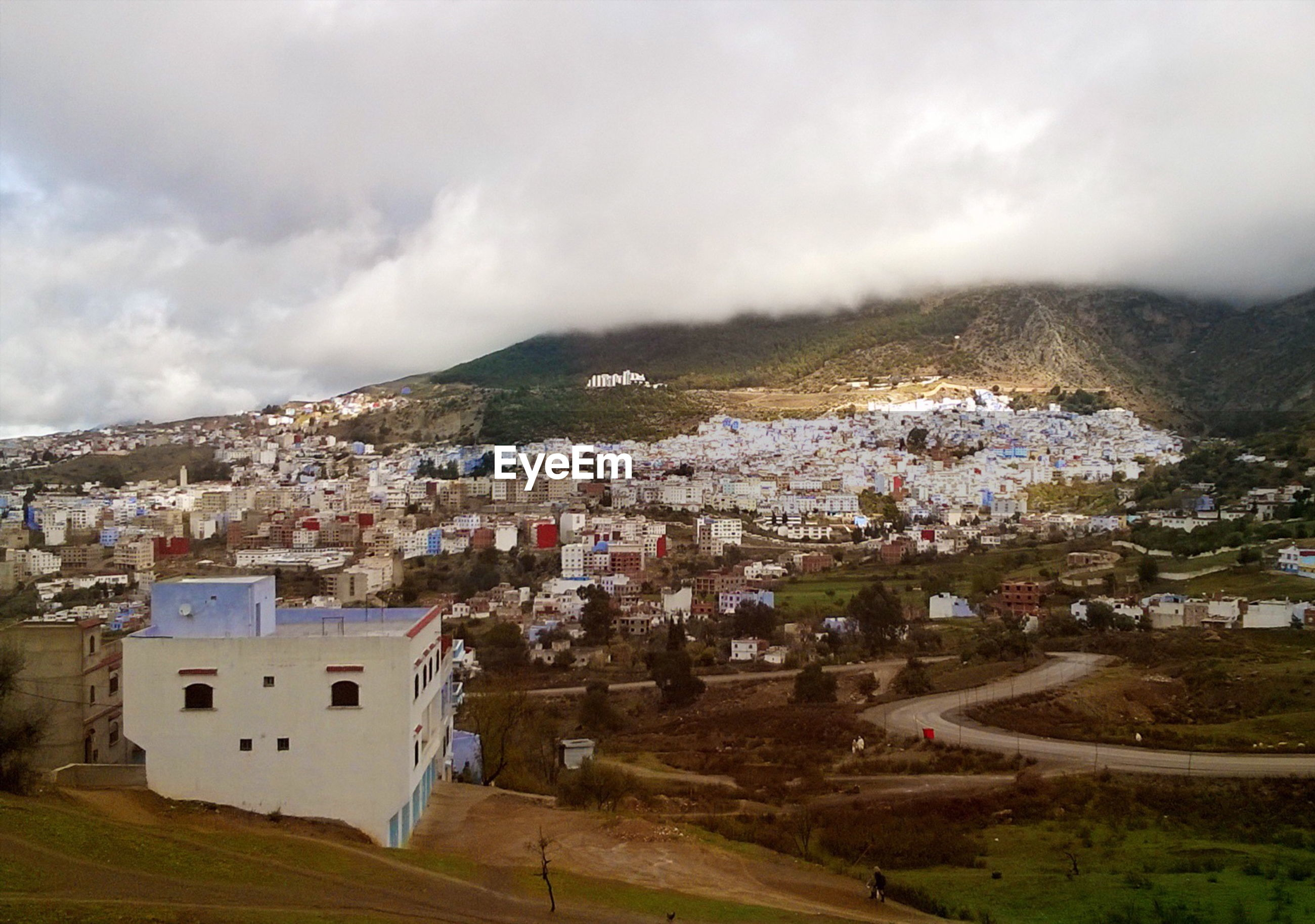 Townscape by mountain against cloudy sky