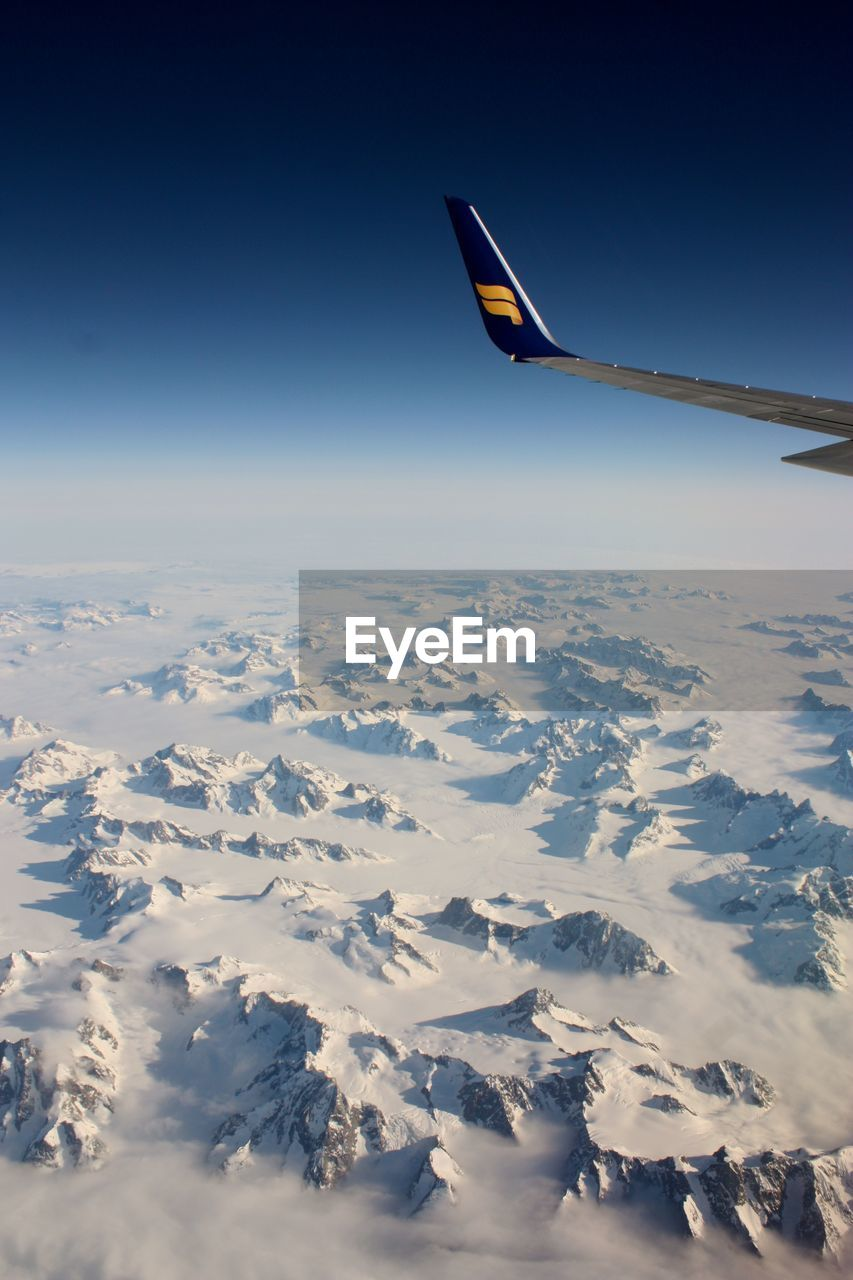nature, winter, cold temperature, sky, beauty in nature, snow, outdoors, scenics, tranquil scene, transportation, blue, mid-air, tranquility, clear sky, no people, flying, landscape, day, airplane, airplane wing