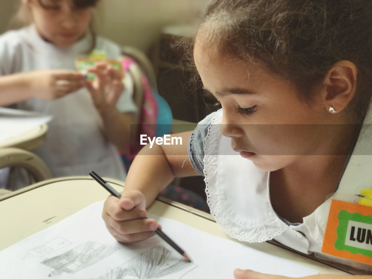 Girl With Name Tag Drawing On Paper At Desk In School