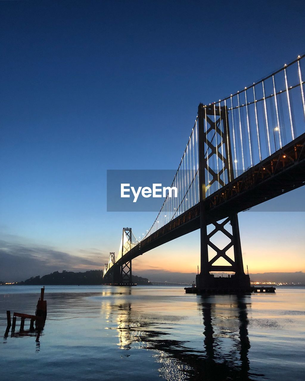 sky, bridge, bridge - man made structure, water, built structure, connection, architecture, transportation, nature, clear sky, suspension bridge, engineering, copy space, travel destinations, sunset, blue, tourism, reflection, waterfront, outdoors, bay