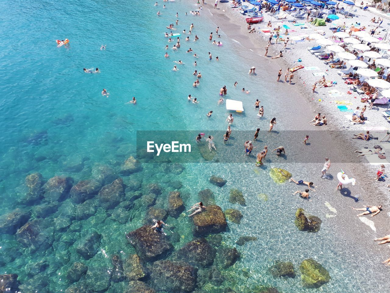 water, sea, group of people, high angle view, beach, land, large group of people, crowd, rock, nature, swimming, solid, day, women, vacations, rock - object, real people, trip, holiday, turquoise colored, outdoors