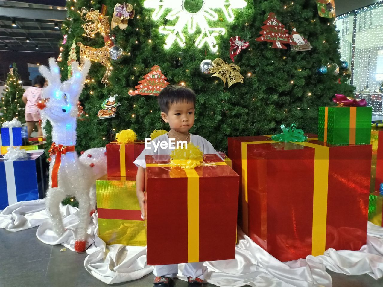 childhood, child, christmas, males, boys, holiday, gift, men, real people, celebration, one person, christmas tree, tree, front view, lifestyles, decoration, innocence, gift box