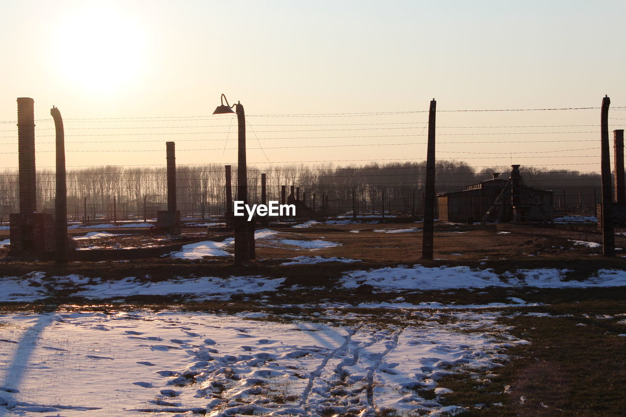 snow, cold temperature, winter, sky, barrier, fence, sunset, boundary, covering, nature, field, beauty in nature, scenics - nature, no people, environment, frozen, tranquility, white color, clear sky, outdoors, wooden post