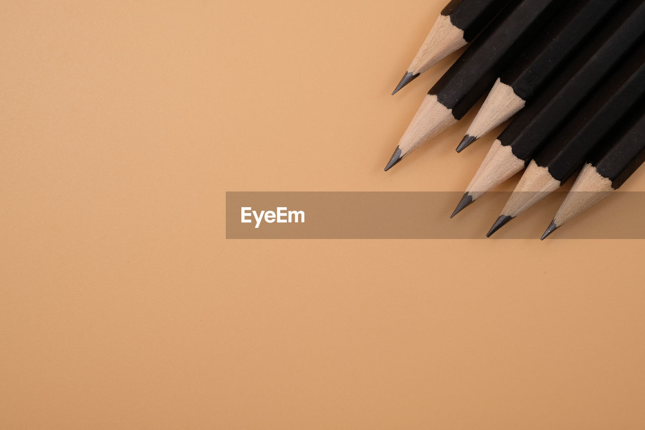 High angle view of pencils on brown background