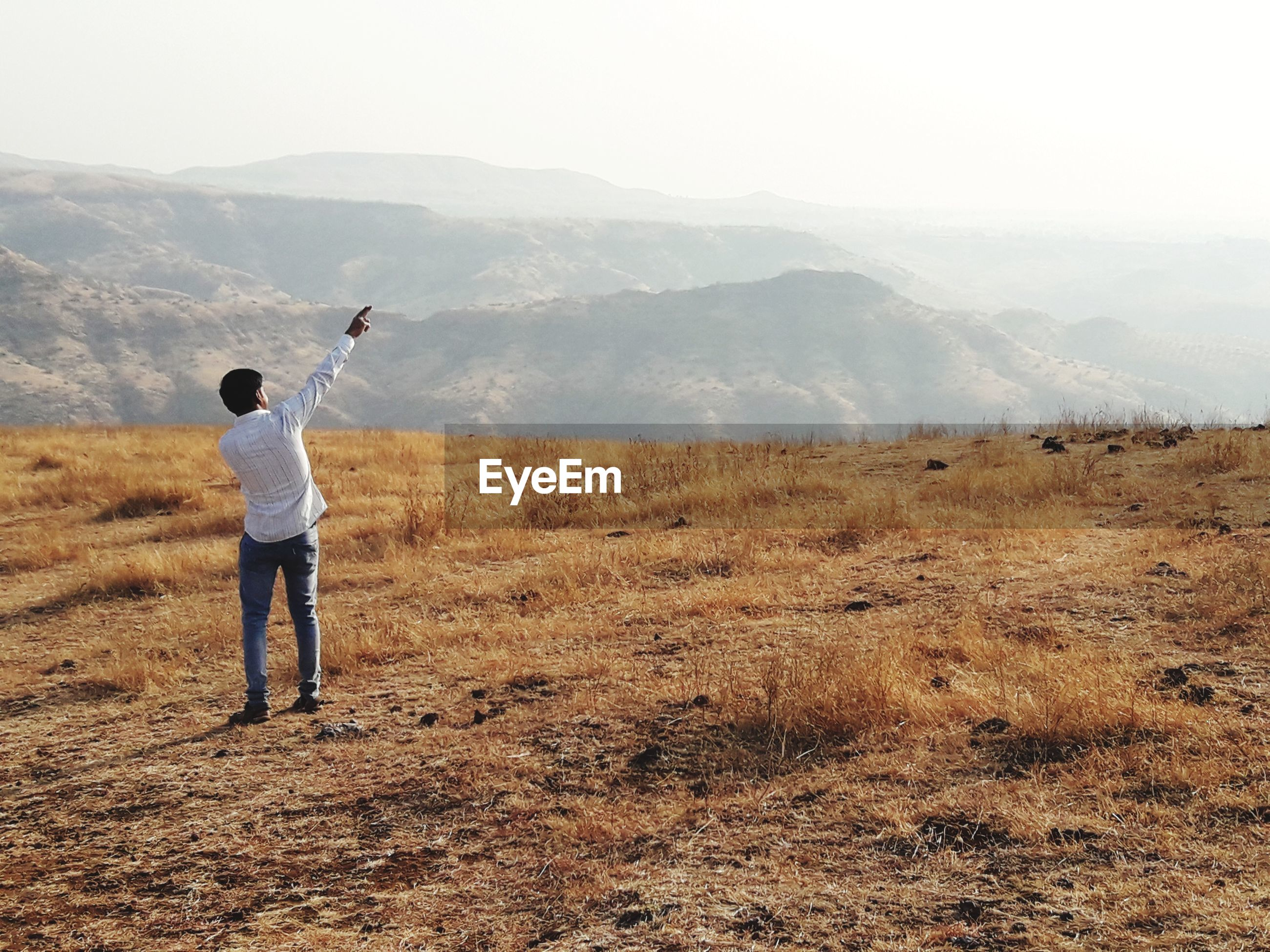 Rear view of man standing on field against mountain