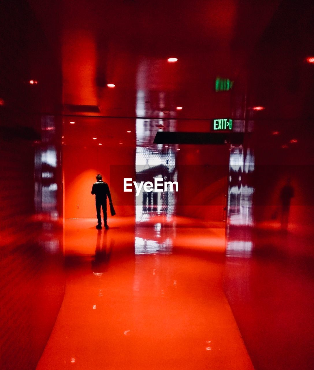 illuminated, real people, text, silhouette, one person, architecture, night, reflection, full length, walking, indoors, lifestyles, communication, built structure, men, people