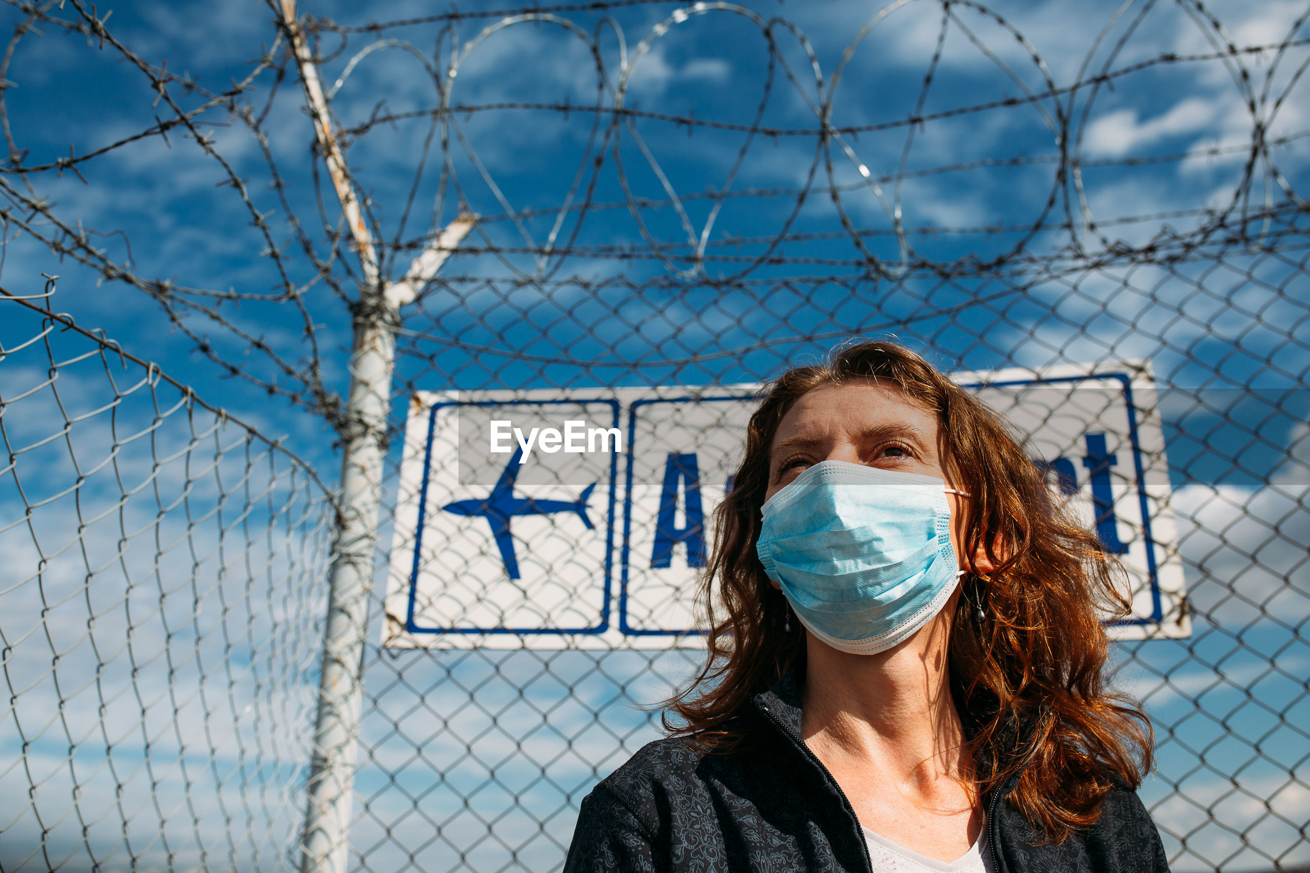 Woman wearing mask while standing by chainlink fence