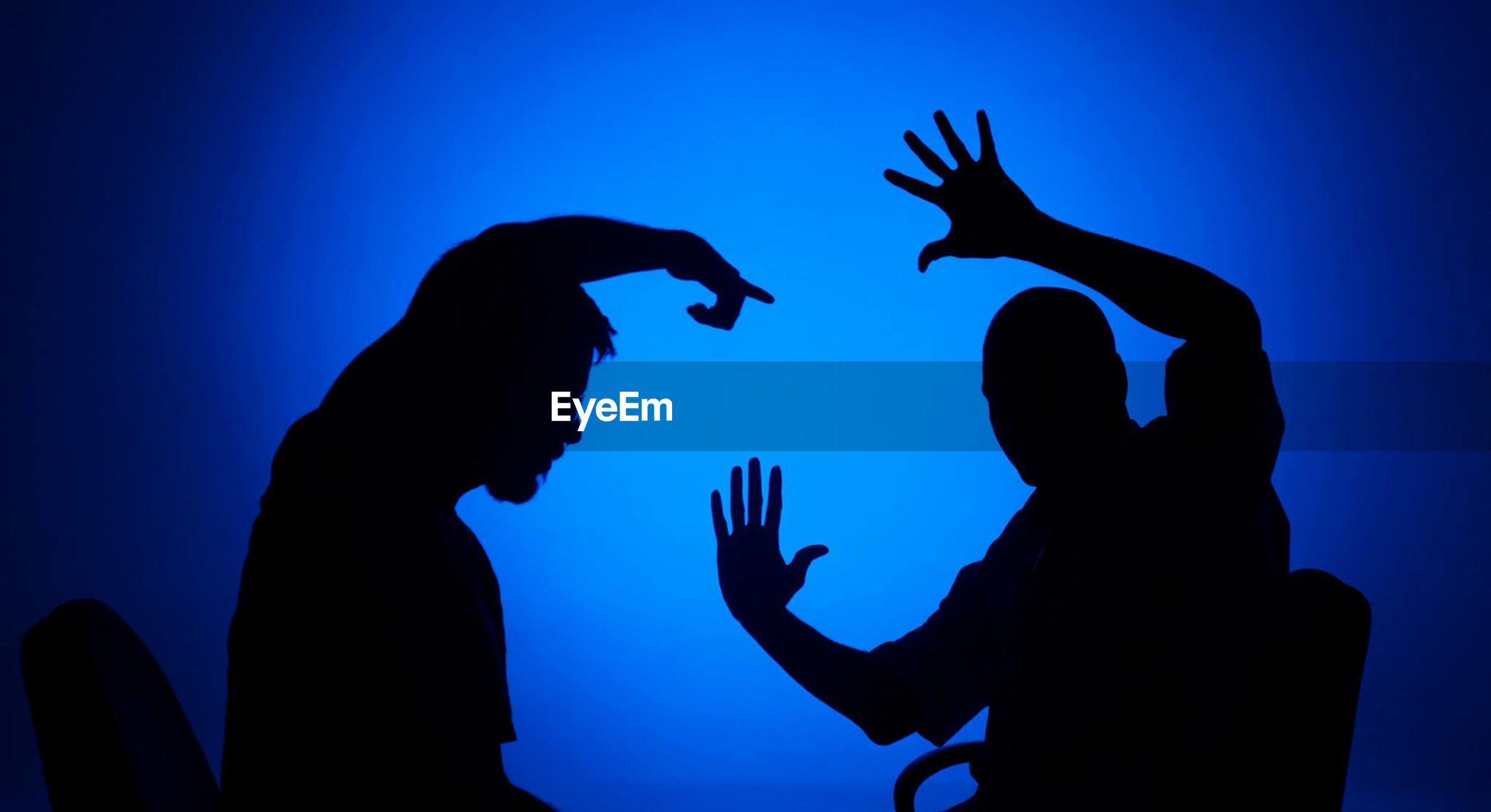 Silhouette friends gesturing over blue background