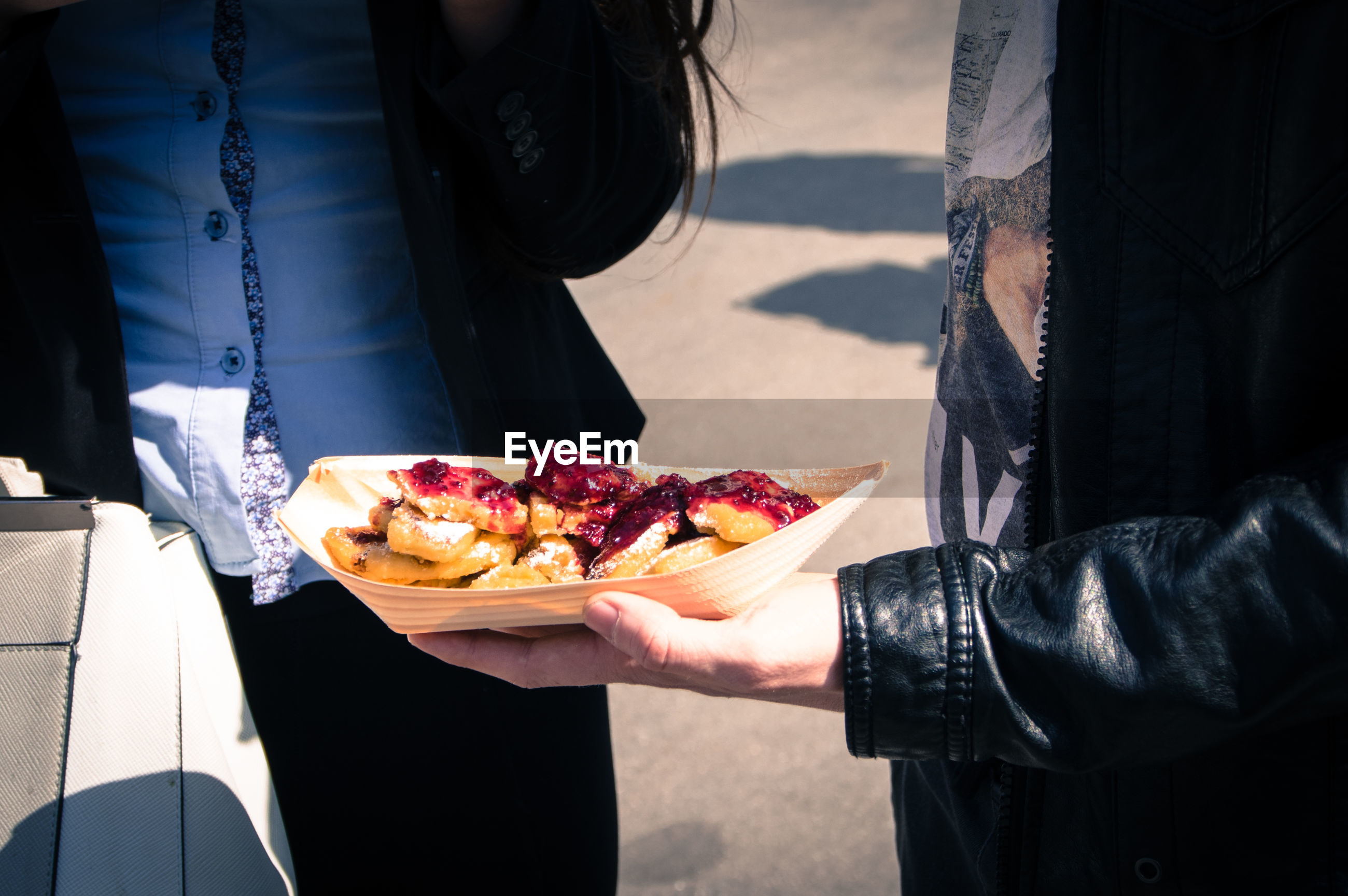 Midsection of man holding food while standing outdoors