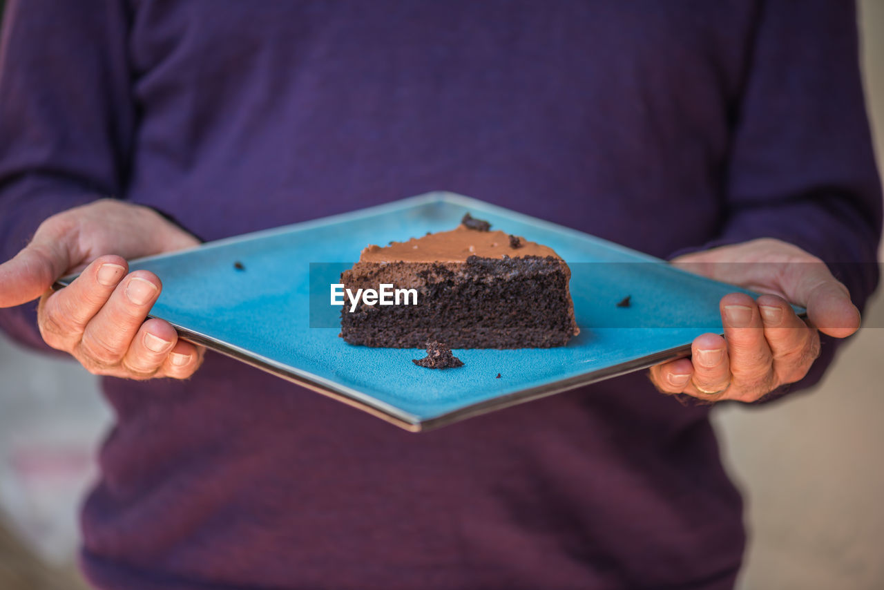 Midsection Of Man Holding Chocolate Cake In Plate