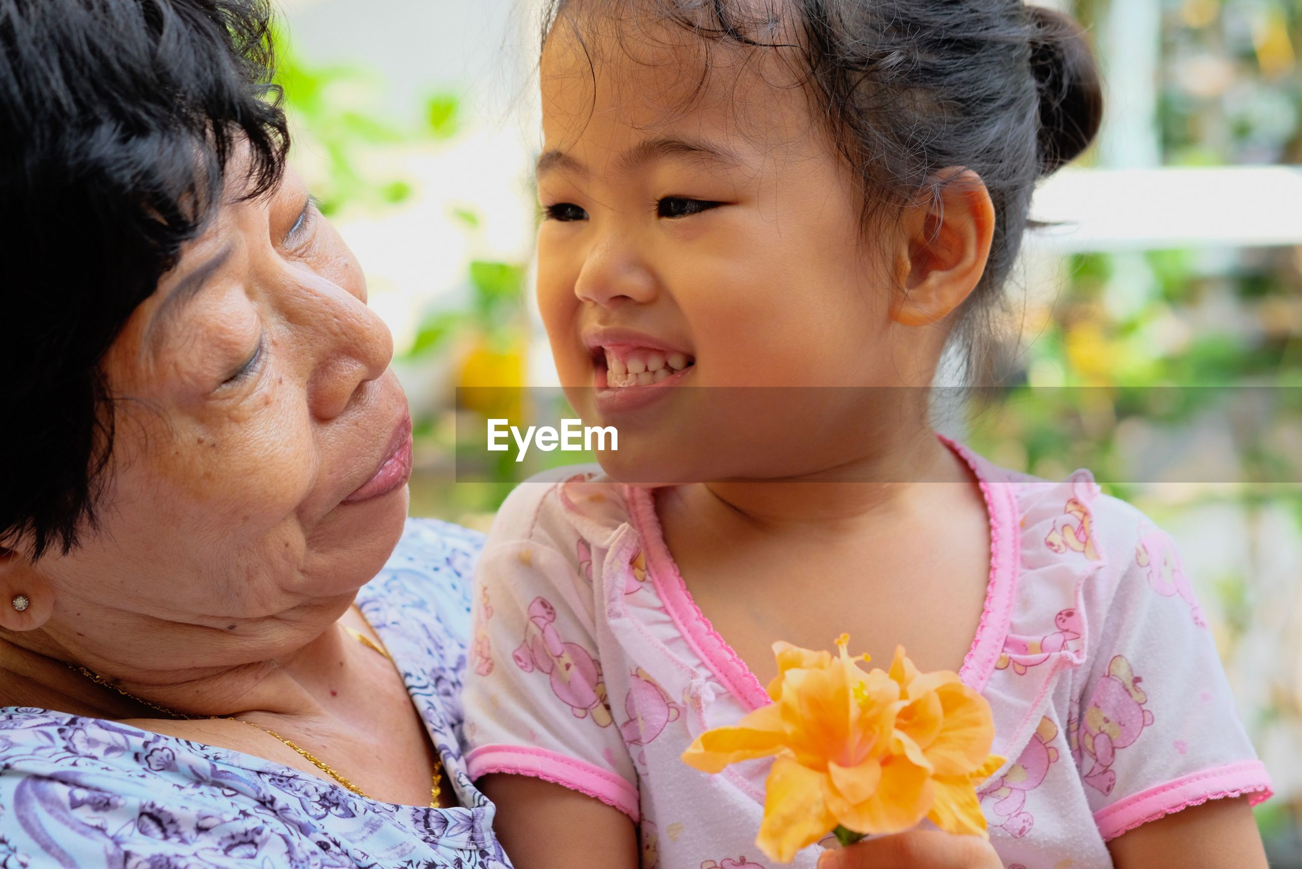 Close-up of grandmother and granddaughter outdoors