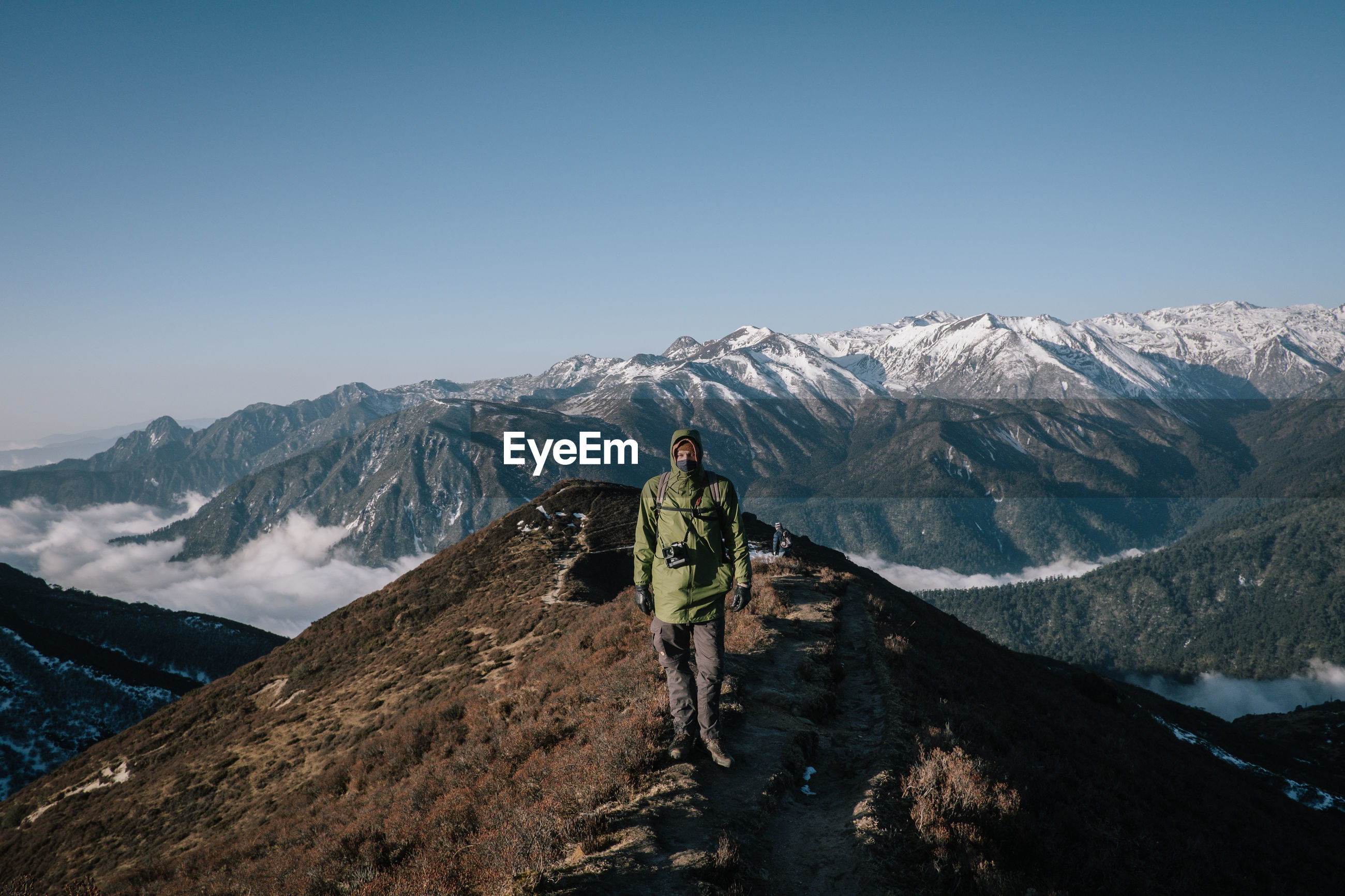 REAR VIEW OF PERSON ON SNOWCAPPED MOUNTAIN AGAINST CLEAR SKY