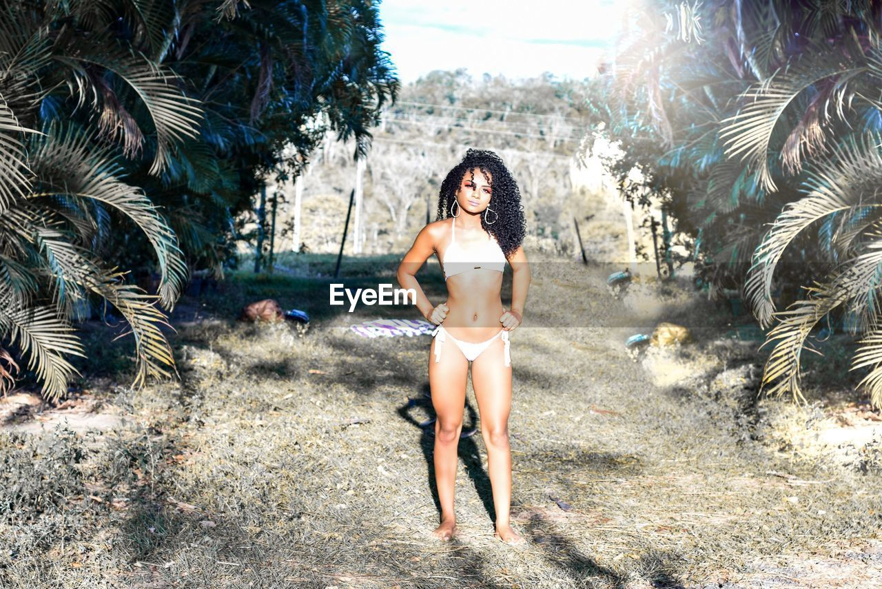 Full length portrait of seductive woman wearing bikini standing in park