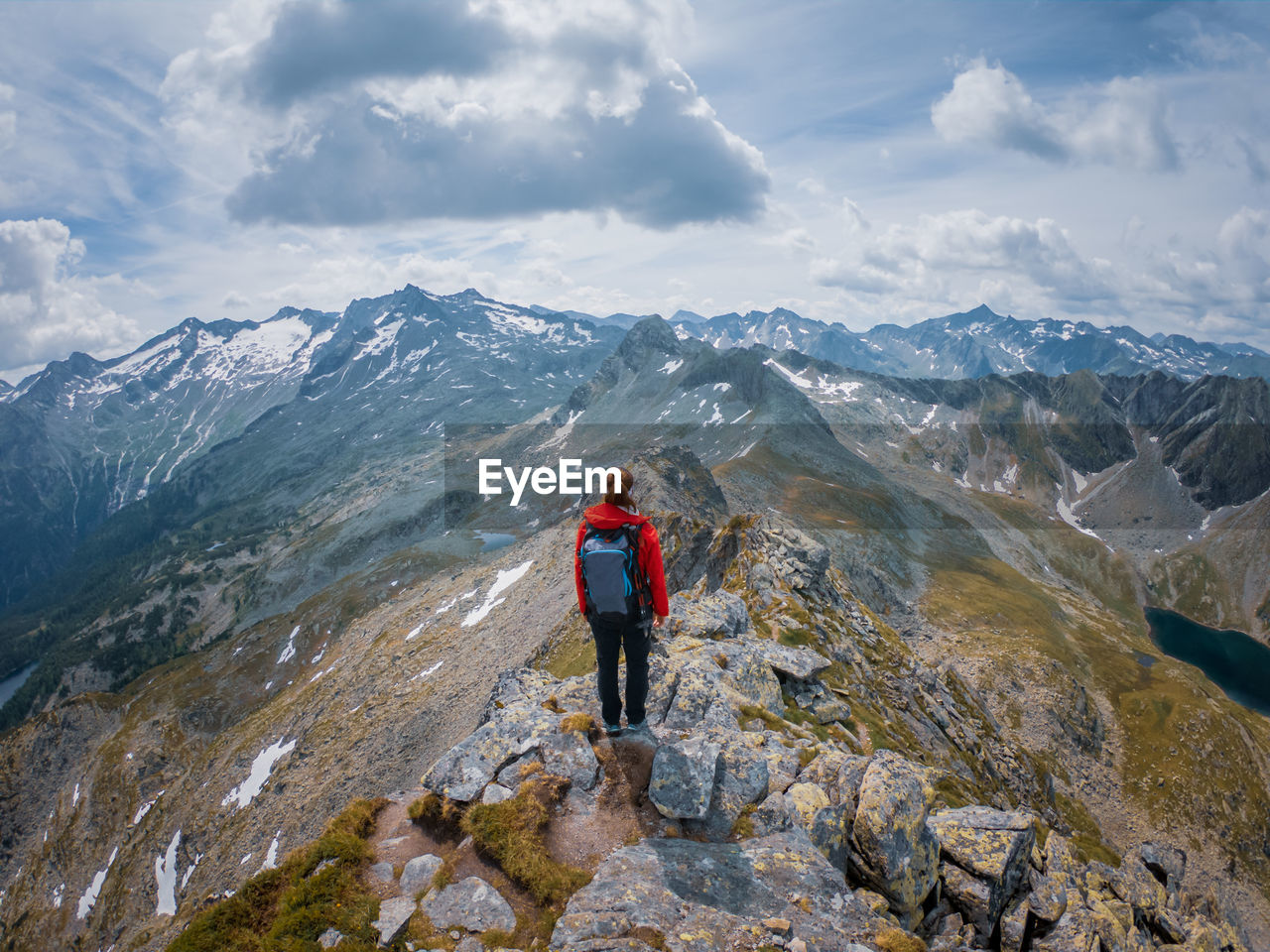Rear view of woman hiking on rocky mountain peak against sky