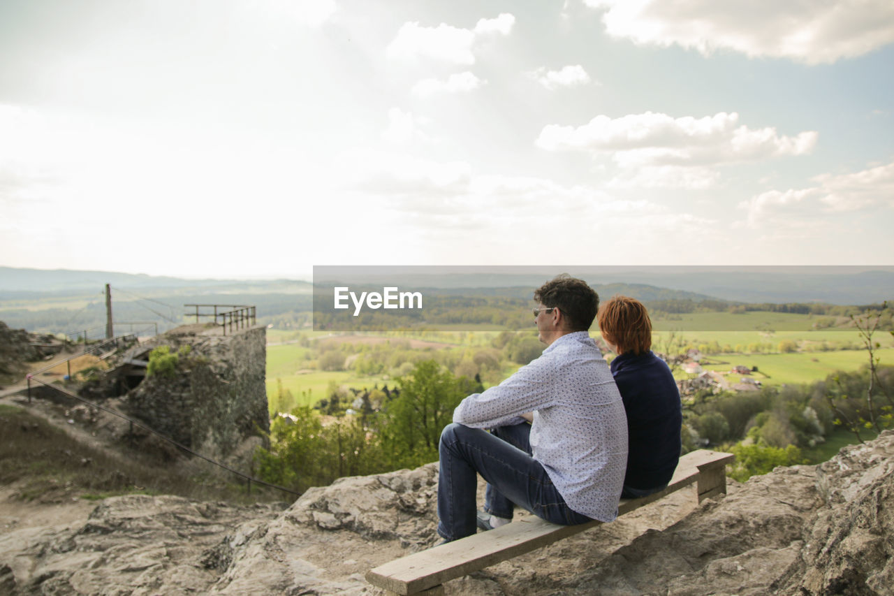 Man And Woman Sitting On Bench Against Sky