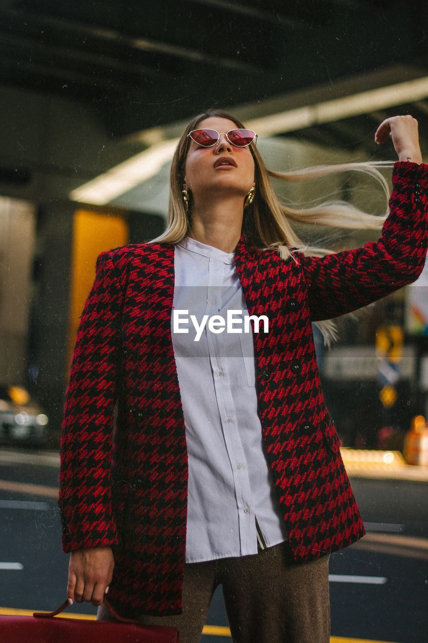 one person, standing, three quarter length, front view, glasses, young adult, real people, young women, leisure activity, architecture, lifestyles, looking, casual clothing, transportation, car, women, looking away, clothing, hair, fashion, hairstyle, outdoors, beautiful woman, human arm