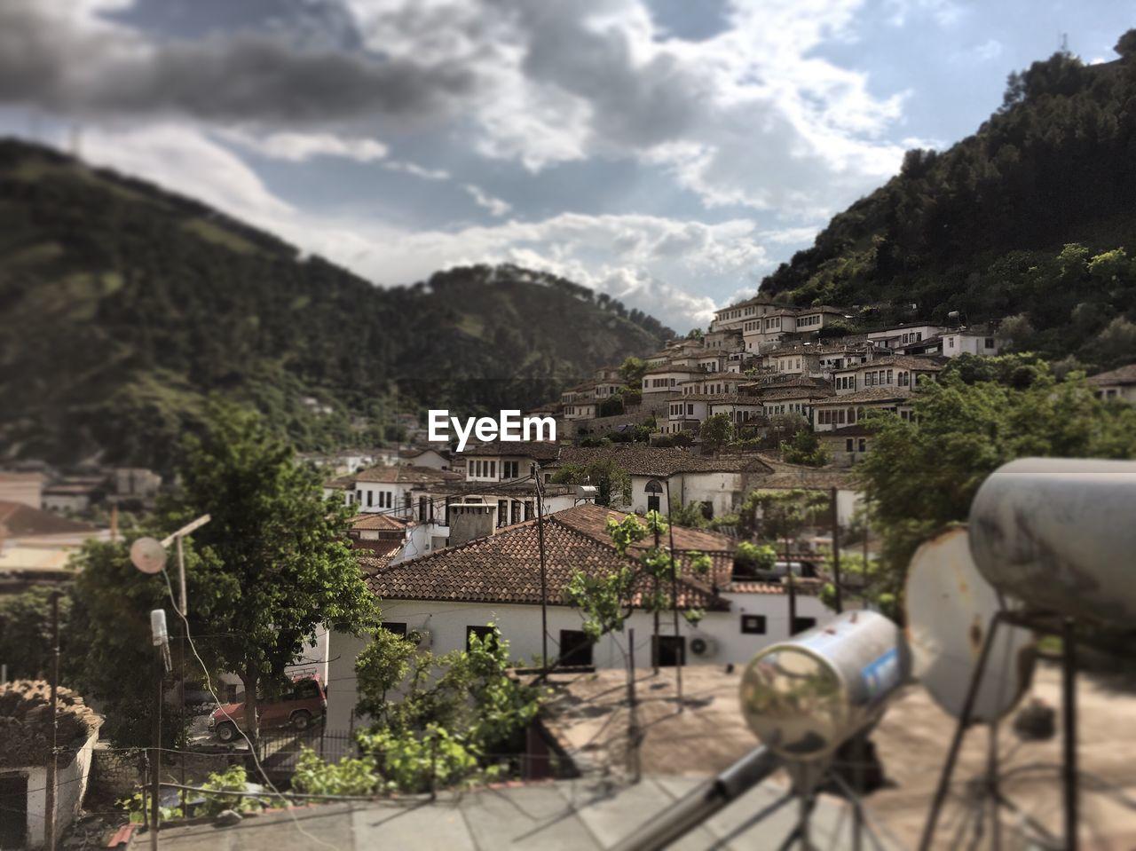 Tilt-Shift Image Of Houses In Town Against Sky