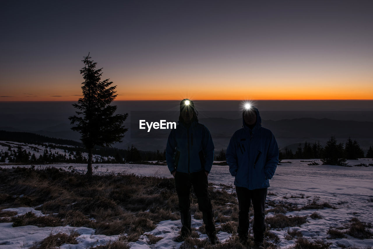 Friends Standing With Flashlights Against Sky During Sunset