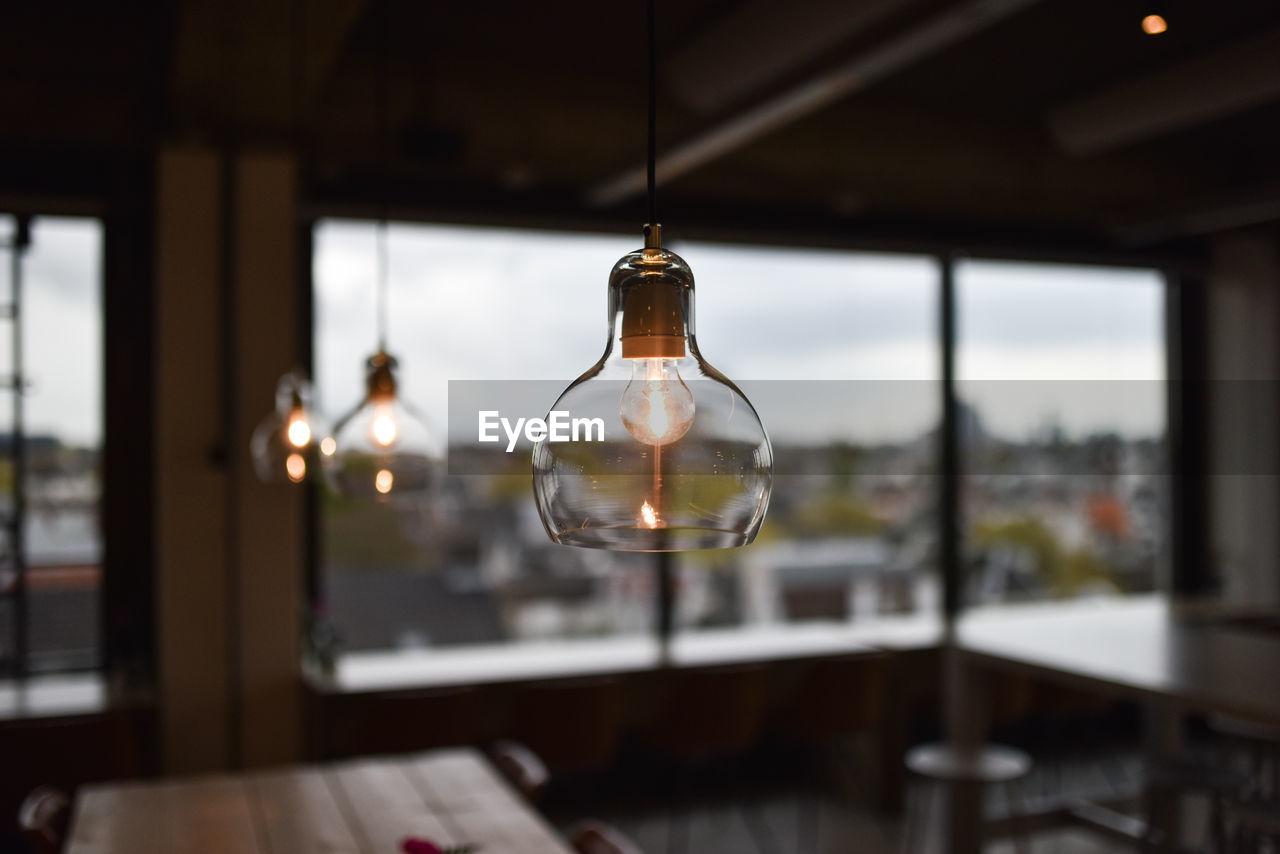 Illuminated Pendant Light Hanging In Restaurant