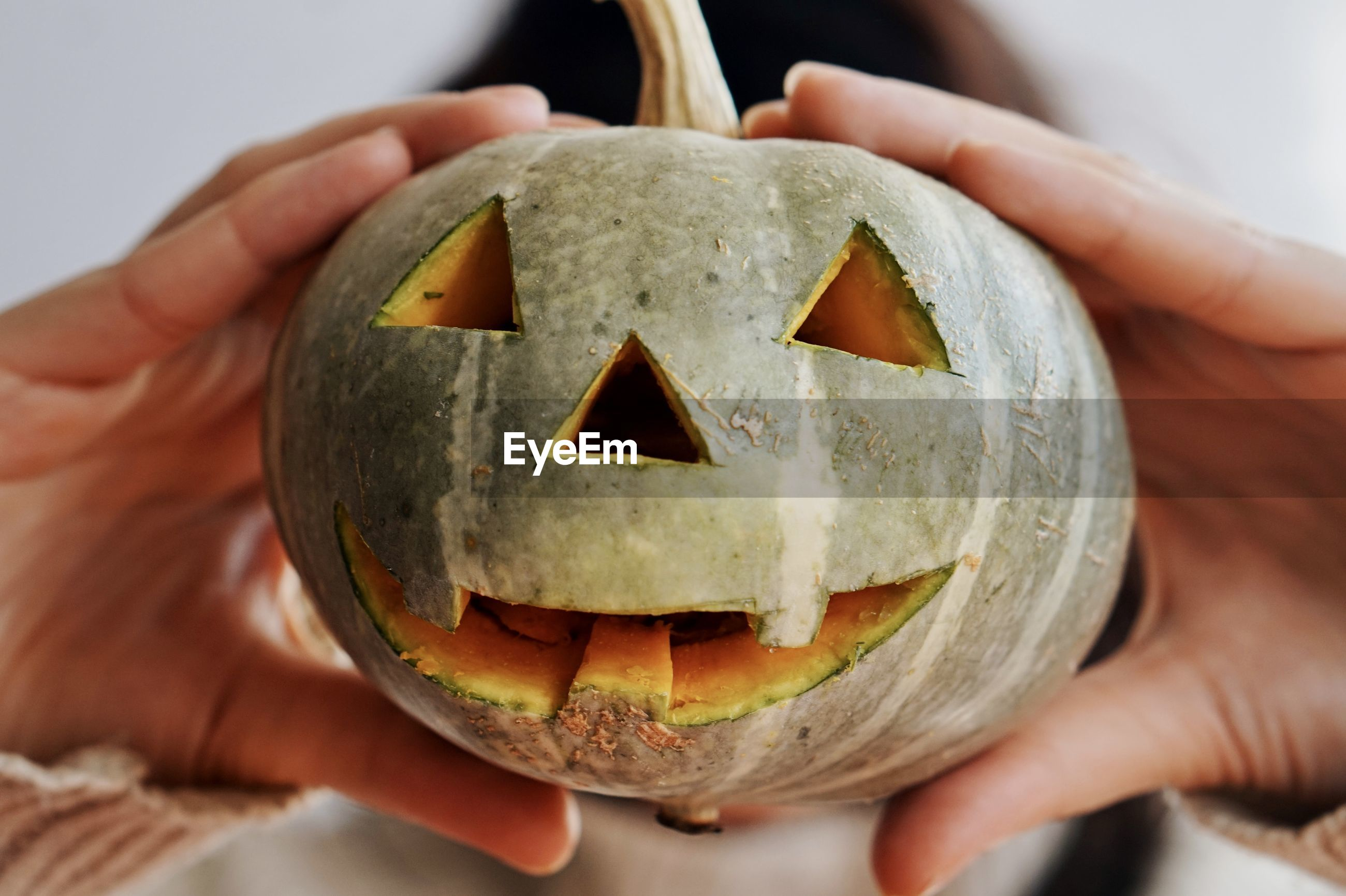 CROPPED IMAGE OF HAND HOLDING PUMPKIN AT HALLOWEEN