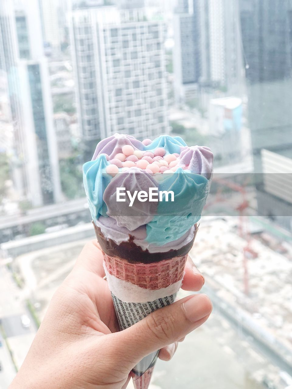 human hand, sweet food, sweet, human body part, food and drink, ice cream, indulgence, food, frozen food, dairy product, holding, hand, dessert, focus on foreground, real people, one person, frozen, temptation, personal perspective, cone, outdoors, finger, frozen sweet food